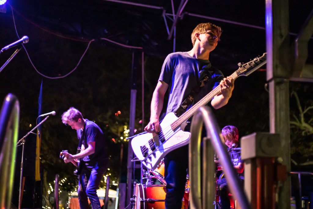 Scott Luxton playing bass guitar performing with Claiming It Anyway at the Manly Harbour Village Halloween Street Party of 2019